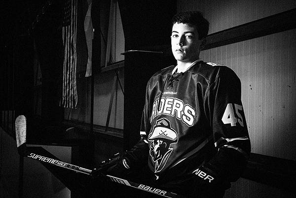 A black and white hockey portrait with American Flag in the background